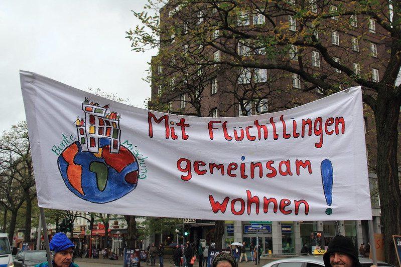 """""""Mieszkać razem z uchodźcami"""" - banner z demonstracji w Hamburgu 2014 (flickr)"""